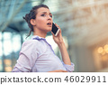 Young woman busy with calling, chatting on the cell phone side view portrait. 46029911