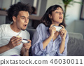 Image of young loving couple in kitchen at home indoors. Eating pizza and playing games with console 46030011