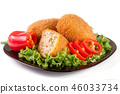 three fried breaded cutlet with lettuce on a black plate isolated  white background 46033734