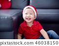 Little boy wearing red santa hat smiling 46038150