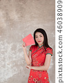 woman wears traditional dress holding red packet 46038909