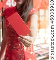 woman wears traditional dress holding red packet 46038910