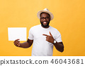 Picture of young smiling african-american man holding white blank board and pointing on it, on 46043681