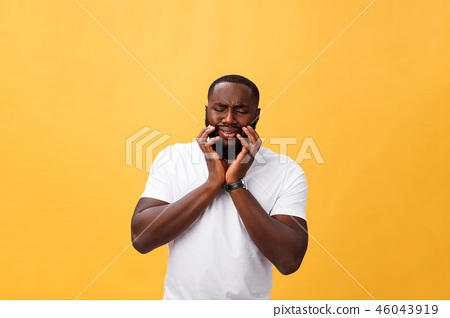 Young Stressed man with hand on his face showing sadness and despair. Isolated over yellow 46043919