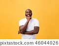 Portrait of a modern young black man smiling with arms crossed on isolated yellow background 46044026