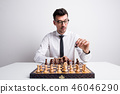 Portrait of a young man in a studio, playing chess. 46046290