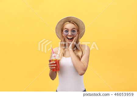 Fabulous woman in sunglasses wearing white t-shirt while holding glass of juice isolated over yellow 46053959
