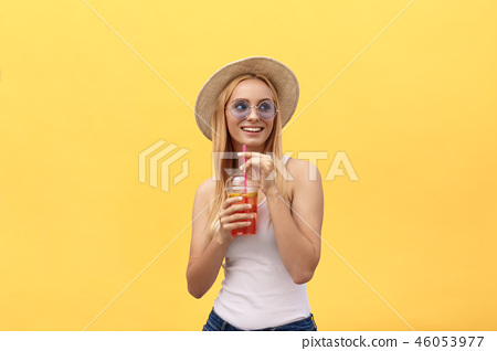 Fabulous woman in sunglasses wearing white t-shirt while holding glass of juice isolated over yellow 46053977