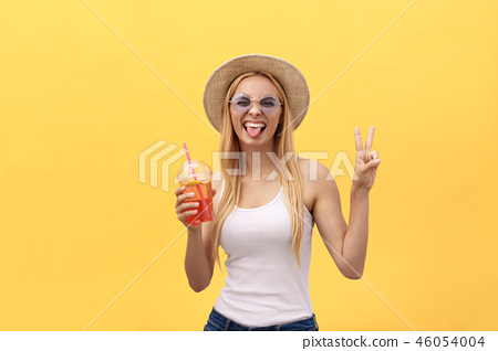 Fabulous woman in sunglasses wearing white t-shirt while holding glass of juice isolated over yellow 46054004