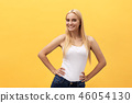 Young charming blond woman with happy exited emotional face looking at camera, isolated over yellow 46054130