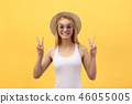 Image of cheerful caucasian woman wearing casual clothing smiling and showing peace sign with two 46055005