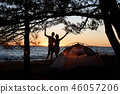 Young couple man and woman having rest at tourist tent and burning campfire on sea shore near forest 46057206