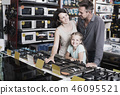 Young family of three choosing new cooking plate 46095521