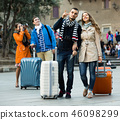 Tourists with luggage walking by street. 46098299