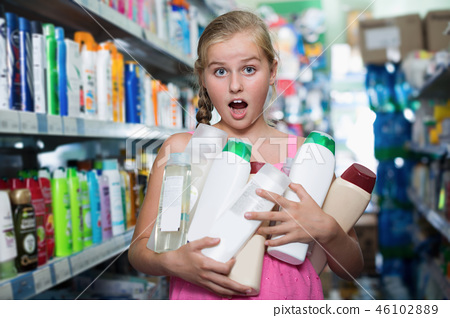 Portrait of happy girl holding a lot of shower gel 46102889