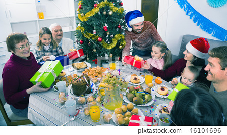 Large family exchanging gifts during Christmas dinner 46104696