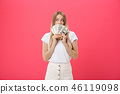 Portrait of a cheerful young woman holding money banknotes and celebrating isolated over pink 46119098