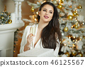 smiling woman holding glass of sparkling wine 46125567