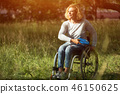 Woman in wheelchair throws frisbee 46150625