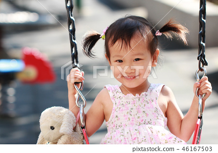 一位開心的亞洲女孩在公園盪秋千 46167503