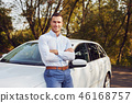 Man with crossed arms stands in front of his car 46168757