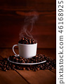 A cup full of hot coffee beans on a wooden table 46168925