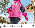 Cute ittle caucasian girl in sport winter jacket having fun playing outdoors with snow. Bird feeder 46170826