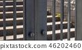 Gate with keyholes leading to a sunlit stairs 46202460