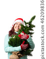 Photo of woman in Santa's cap with Christmas tree in hand 46209836