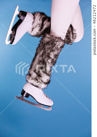 Woman legs wearing ice skates fur socks, skating 46212472