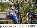 Senior man with electrobike sitting on a bench outdoors in town, using smartphone. 46218895