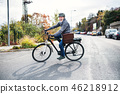 Active senior man with electrobike cycling outdoors in town. 46218912