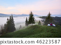 Silhouette of girl in tourist tent on grassy hill on foggy valley, pine trees and distant mountain 46223587