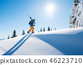 Low angle shot of a skier walking on top of the mountain with his skis on his shoulder on a sunny 46223710