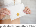 Closeup woman with slim body in lace underwear holding invitation card in hand, back view 46223942