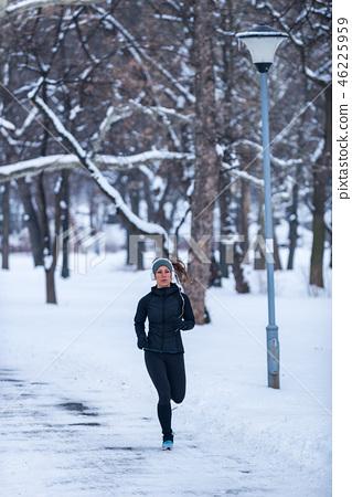 Female athlete jogging in park in winter 46225959