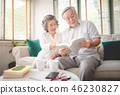 Happy senior couple sitting at sofa reading a book 46230827