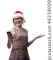 Image of blonde in glasses and Santa's cap with phone in hand on empty space 46238099