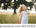 Little girl in sky blue dress stand in field in front of big tree 46240992