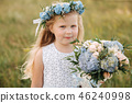 Little girl in sky blue dress with wreath and bouquet stand in field in front of big tree 46240998