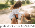 little girl playing with mom in the park in summer day during the sunset 46241058