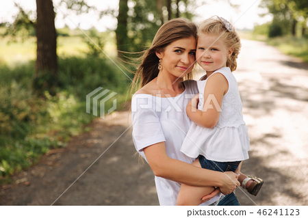 Attractive Mom and blonde hair daughter sits on road near big alley. They smile and look to natune 46241123