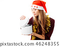 An interested girl in a Santa hat, looks gift box 46248355