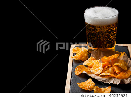 Glass of lager beer with potato crisps snack  46252921