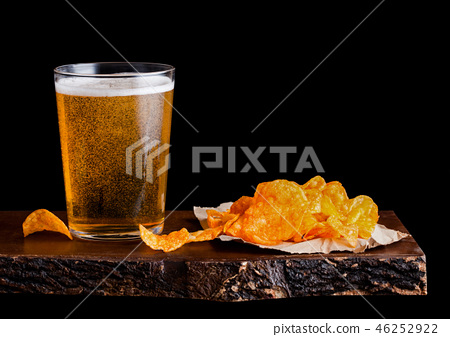 Glass of lager beer with potato crisps snack  46252922