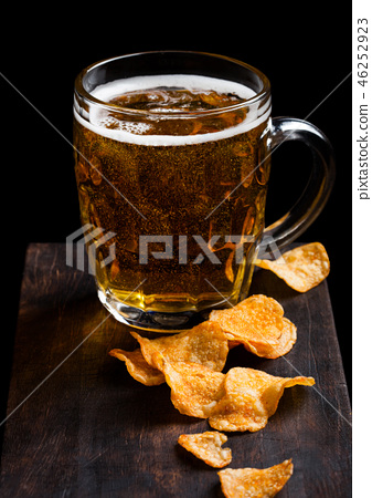 Glass of lager beer with potato crisps snack  46252923