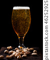 Glass of lager beer with pistachios nuts on stone  46252925