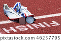 Track spikes with medals at the finish line 46257795