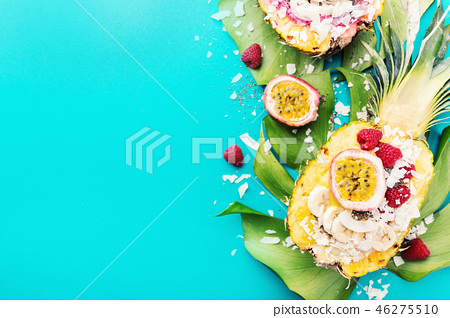 Smoothie bowls served in cut pineapple on blue 46275510