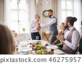 A man giving a bottle of wine to his father on indoor birthday party, a celebration concept. 46275957